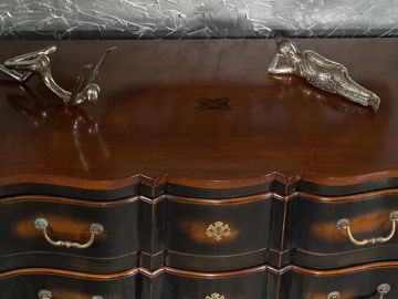 The beveled edges and curves of the bottom apron, the fake lock as accent on the center of drawer.