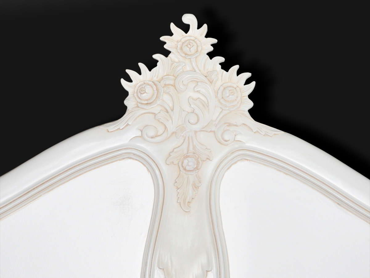Wood carving cresting the headboard